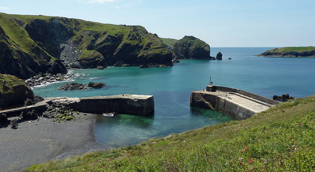 Mullion Cove Harbour on a clear summers day. Green hills and clear blue water.
