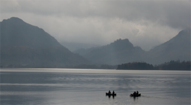 A group canoeing on Derwent Lake in the Lake District