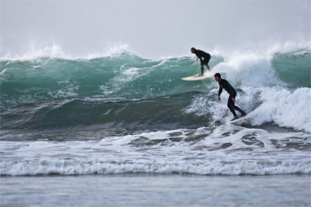 Two surfers riding a wave