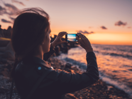Girl taking photo of ocean.