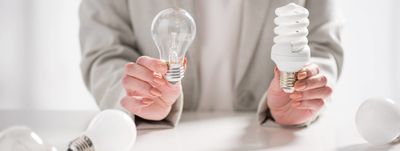 Person holding led light bulb and traditional light bulb