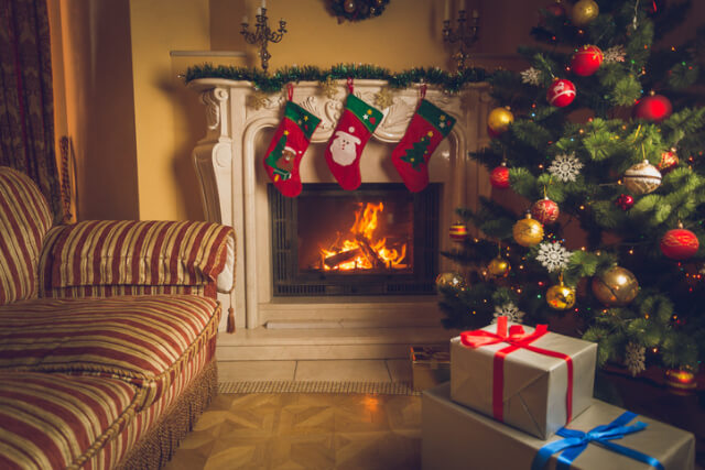 Christmas tree, presents and stockings by open fire