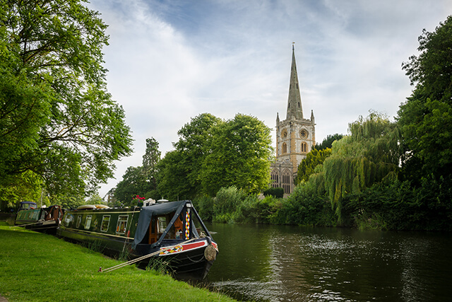 Boat on the banks of the River Avon, with a view of Holy Trinity Church, Stratford-Upon-Avon