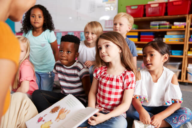 Teacher reading a book to the class