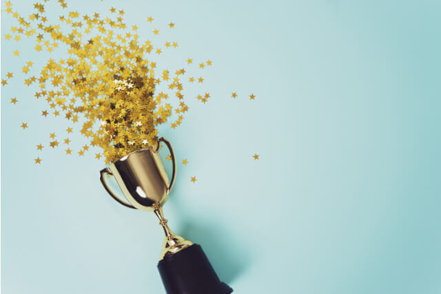 Trophy exploding with star confetti