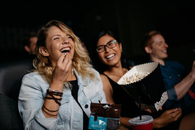 friends laughing and eating popcorn in a cinema