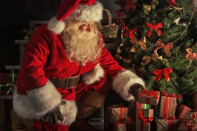 Santa giving presents under tree