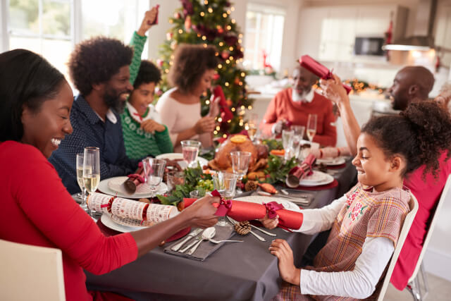 family pulling christmas crackers at table
