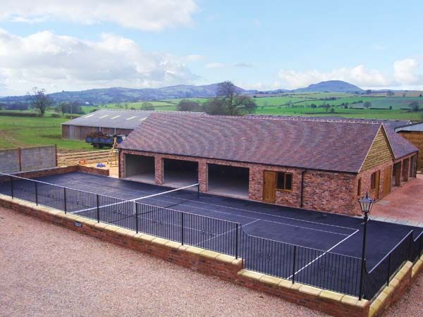 The tennis court at The Old Cow House (Reference 3591) in Plaish.