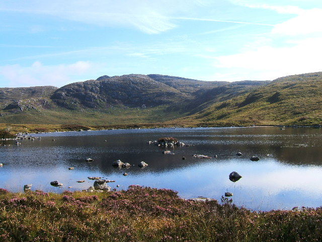 Scottish highlands; clear blue sky, green mountains and a reflective lake