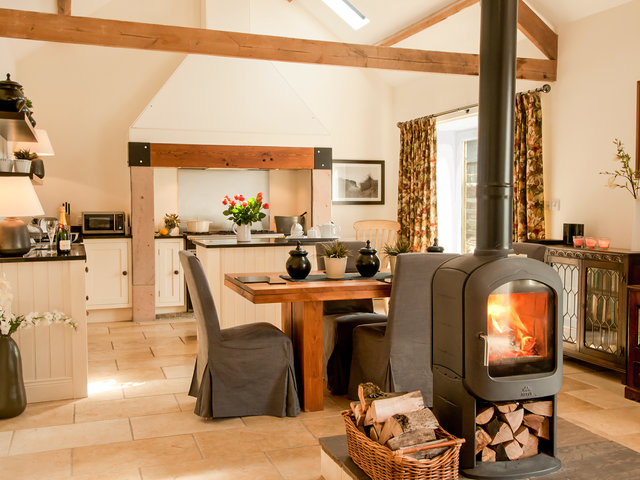 Open plan living area with wood burning stove and character features including exposed beams