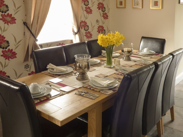 Dinning table and chairs, set up ready for a meal with daffodils on the table.