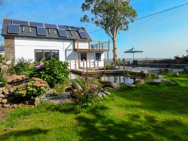 Property with solar panels and lots of greenery.