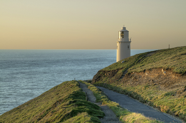 White lighthouse located on a coastal clifeside coastal path with green hills, blue water and a creamy sky at sunset