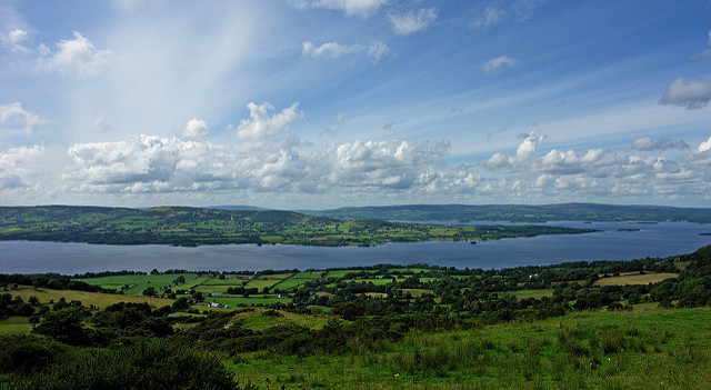 Landscape image of a blue lake amongst green hills and a cloudy blue sky