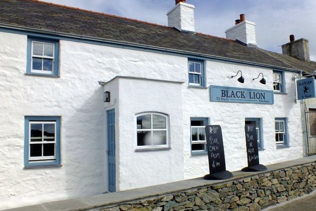 Pub with white tones walls and blue trim around the doors and windows